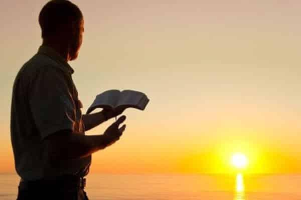 homem lendo a bíblia no por do sol