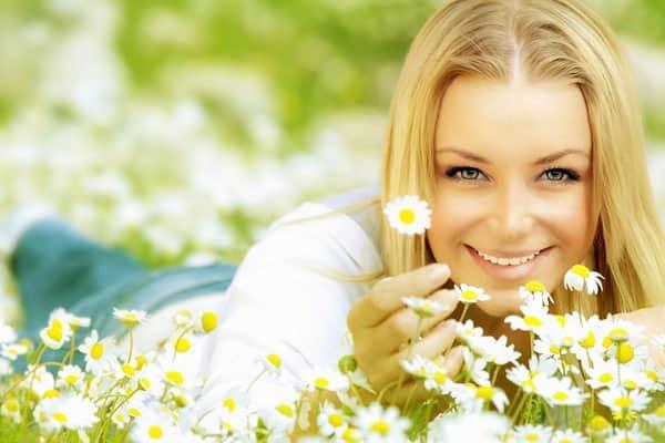 mulher radiante deitada no jardim segurando uma margarida branca